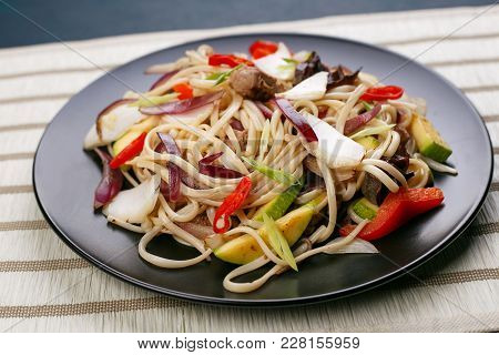 Udon Wok Noodles With Pork And Peppers, Served On Black Plate, Close Up. Japanese Cuisine, Restauran