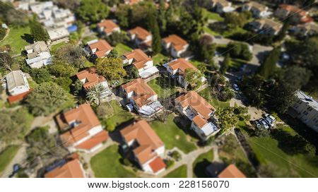 Red Houses Rooftops With Green Grass In The Suburb Of Israel. Tilt Shift Bokeh Effect For A Miniatur