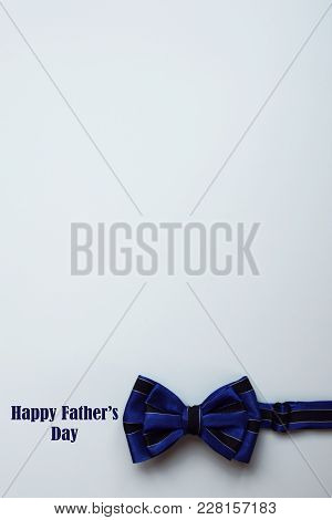 Dark Blue Bow Tie With Black Stripes On Light Blue Background. Happy Fathers Day Concept. Template F