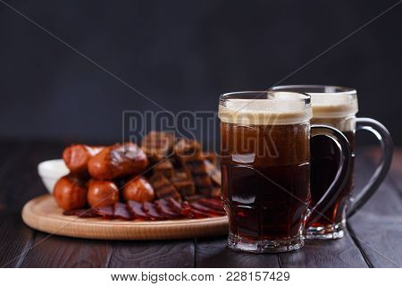 Dark Beer And Appetizing Beer Snacks Set. Two Mugs Of Stout, Wooden Board With Grilled Sausages, Bas