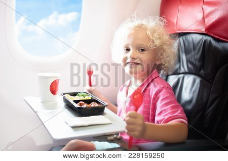 Child In Airplane. Kids Fly. Children Flight Meal