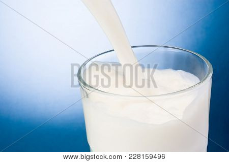 Pouring Milk Into Glass On A Blue Background