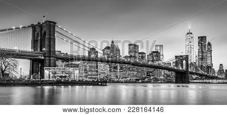 Brooklyn Bridge And New York City Manhattan Downtown Skyline At Dusk With Skyscrapers Illuminated Ov
