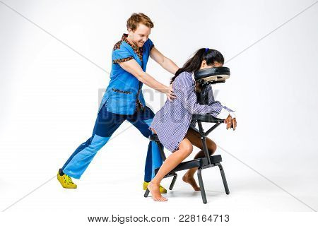Theme Massage And Office. A Young Man With Smiling Therapist In Blue Suit Is Doing Back And Neck Mas