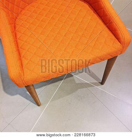 Bright Orange Armchair On Tile Floor. Modern Style With A Retro Feel.