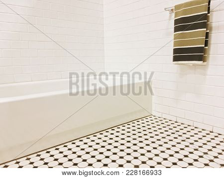 New Bathroom With Black And White Ceramic Tile Decor And A Striped Towel On The Wall.