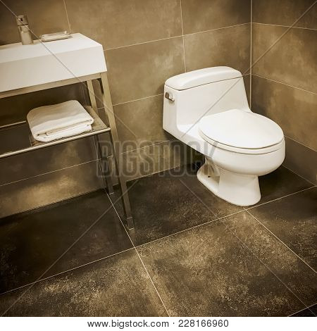 Modern Bathroom With Sink And Toilet, And Tiled Walls And Floor.