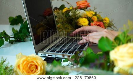 Close-up Of Laptop On Which Hands Of Female Flower Designer Prin