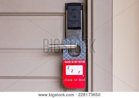 Closed Door Of Hotel Room With Please Do Not Disturb Sign Hang On Door Knob