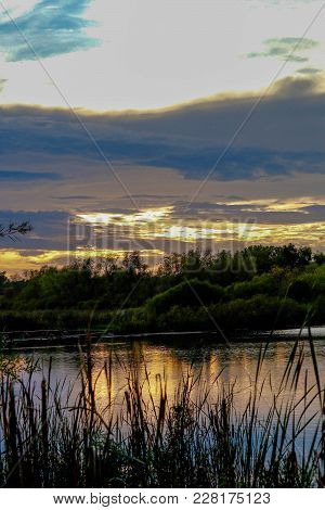 Beautiful Sunset Over A Marshland With A Few Clouds In The Sky