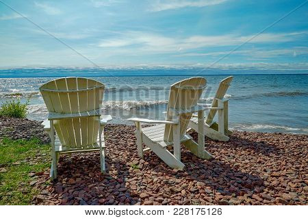 White High Back Lawn Chairs By The Shore At Lake Superior In Minnesota In The Summer