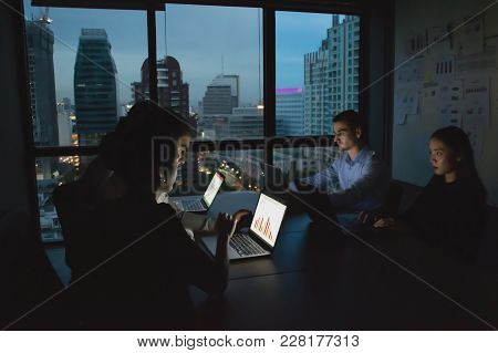 Business Overtime Concepts . Group Of Business People Working Overtime In Nighttime. Businessmen Are