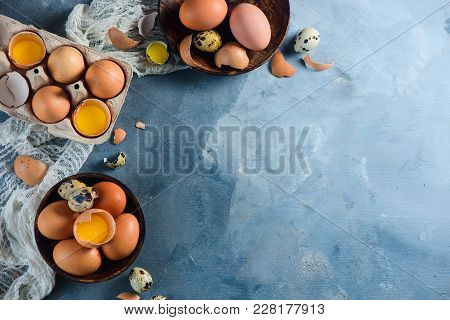 Header With Raw Brown Hen And Quail Eggs, Whole And Broken, On A Wooden Dish And Carton Tray. Concre