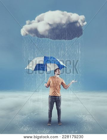 Young Man Holds An Umbrella Under A Rainy Cloud And Checks If Is Still Raining.