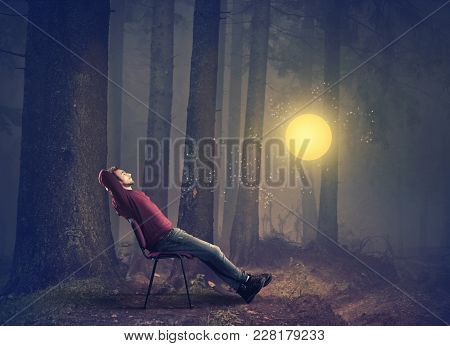 Man Sitting On Chair In The Forest Watching Fairy Light Globe.