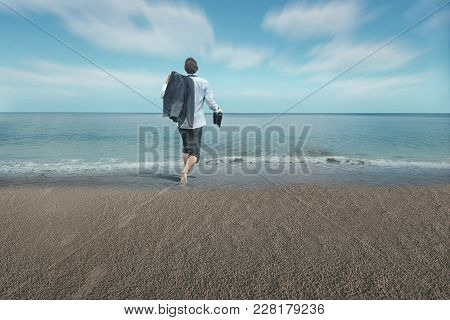 Businessman Running Happy To The Sea . The Concept Of Take A Necessary Break And Enjoy It.