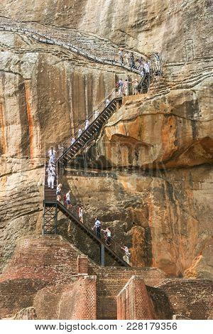 Sigiriya Rock, Sri Lanka - September 6, 2003: Schoolchildren And Tourists On A  Cliff Staircase At T