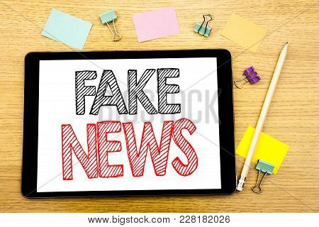 Writing Text Showing Fake News. Business Concept For Hoax Journalism Written On Tablet, Wooden Backg