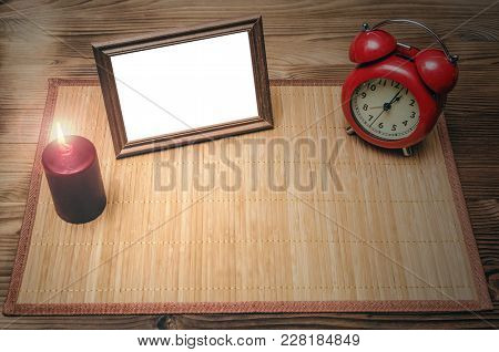 Photo Frame With Copy Space, Red Alarm Clock And Burning Candle On Wooden Desk Table Background With