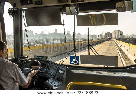 Sao Paulo, Sp, Brazil, December 14, 2017. Bus Driver Drives An Articulated Bus That Travels On The T