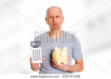 Man In Gray Shirt With Pocket Calculator And Piggybank