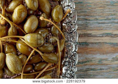 Pickled Caper Berries In Metal Dish . Edible Fruits Of Capparis . Berries Are Used As Garnish.old Wo