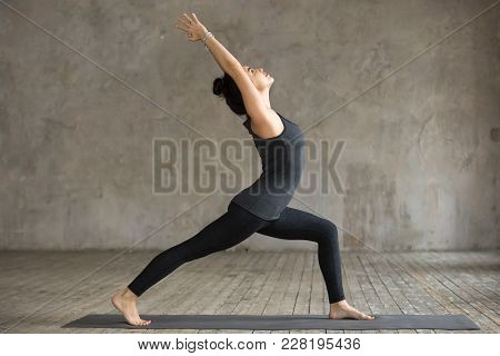 Young Woman Practicing Yoga, Doing Virabhadrasana 1 Exercise, Warrior One Pose, Working Out, Wearing