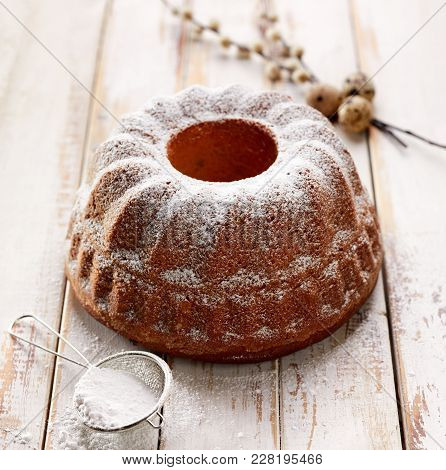 Easter Yeast Cake Sprinkled With Powdered Sugar On A Wooden White Table. Traditional Polish Easter D
