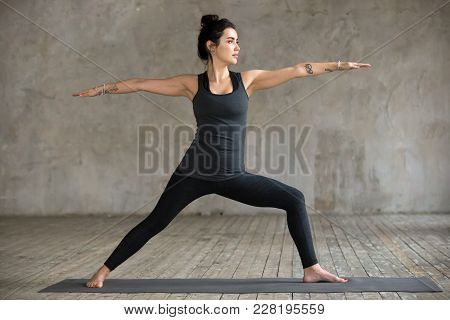Young Woman Practicing Yoga, Doing Virabhadrasana 2 Exercise, Warrior Two Pose, Working Out, Wearing