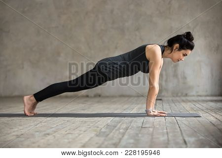 Young Woman Practicing Yoga, Doing Push Ups Or Press Ups Exercise, Phalankasana, Plank Pose, Working