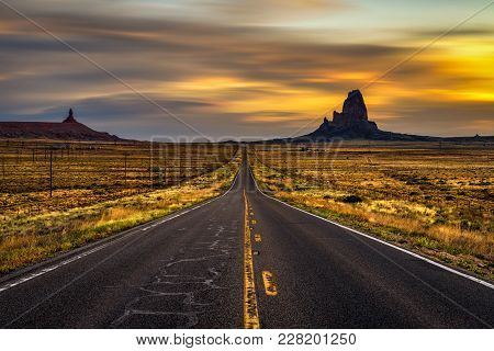 Sunrise Over Empty Straight Road Leading To Monument Valley, Utah, Usa. Long Exposure.