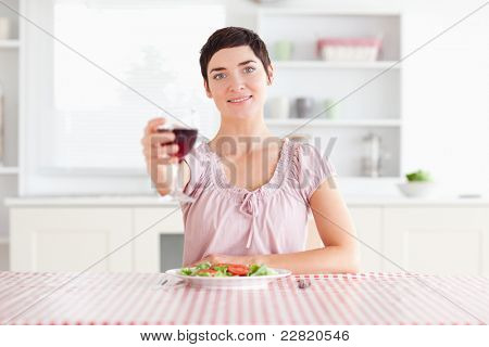Cute Woman toasting with wine in a kitchen poster