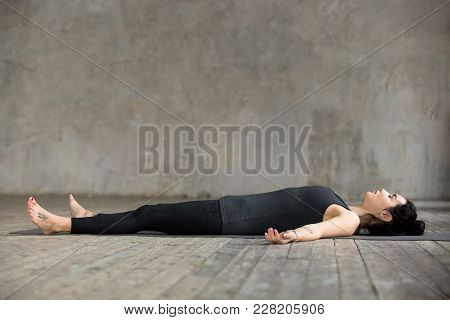 Young Sporty Woman Practicing Yoga, Lying In Dead Body Or Corpse Pose, Savasana Exercise, Working Ou