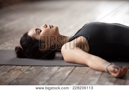 Young Sporty Woman Practicing Yoga, Lying With Eyes Closed In Dead Body Or Corpse Pose, Savasana Exe