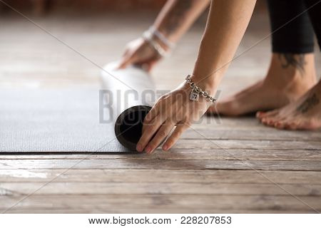 Hands Of An Attractive Young Woman Folding Black Yoga Or Fitness Mat After Working Out At Home In Li