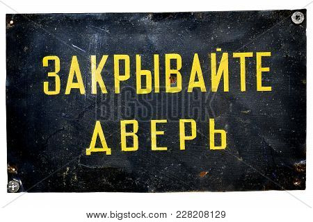 Old Soviet Metallic Plate Screwed To A Door With A Writing: Keep The Door Closed. Isolated On White