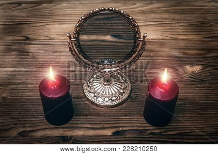Golden Mirror On The Magic Table Between A Two Burning Candles On Both Side On Wooden Desk Table Bac