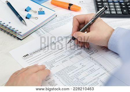 Man Filling Us Tax Form.
