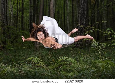 Zero Gravity. Young Beautiful Woman Flying In A Dream In A Summer Forest. White Dress And Hair In Th