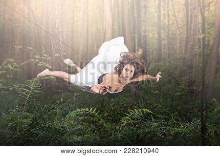 Zero Gravity. Young Beautiful Woman Flying In A Dream. Forest Green And Glow. White Dress And Hair I