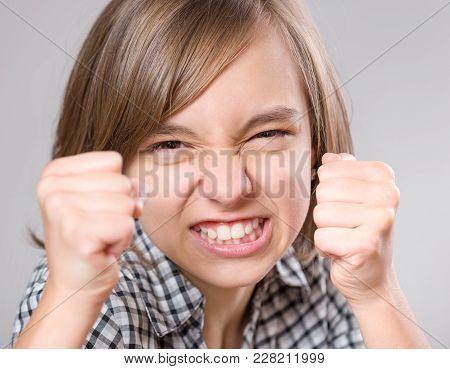 Close-up Emotional Portrait Of Caucasian Angry Child Is Ready To Fight. Beautiful Severe Teenage Gir