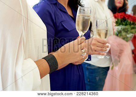 People Holding Glasses Of Champagne And Making Toast. Clinking Glasses Of Champagne In Hands. Happy