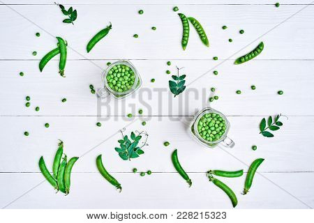 Full Glass Jars With Fresh Green Peas On White Wooden Background, Copy Space. Bio Healthy Food. Gree