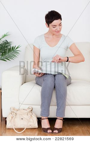 Impatient Woman with a bag and a magazine in a waiting room