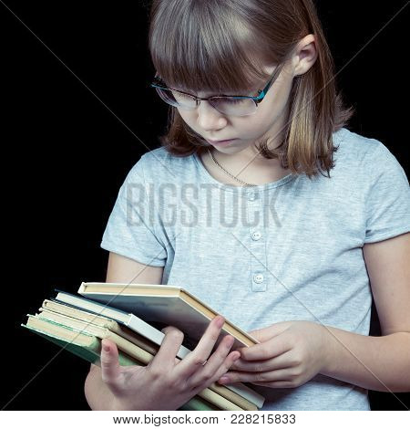 Square Shot Of Teenage Girl In Glasses With Stack Of Books Isolated On Black Background