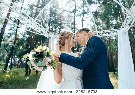The Groom Kisses The Bride At The Wedding Ceremony. The Bride And Groom In Wedding Dresses On Natura