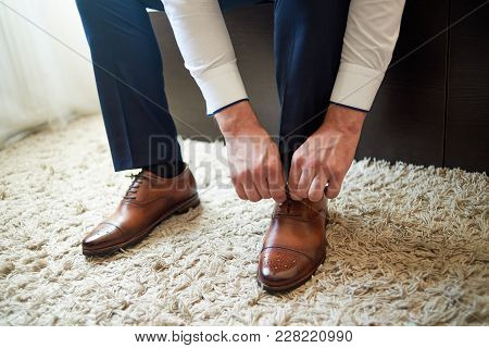 Businessman Tying Shoe Laces Indoors, Close Up. Man Dressing Up With Elegant Leather Shoes. Groom Pr
