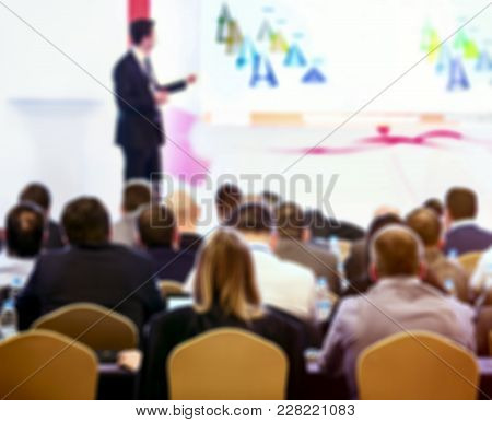 Picture Blurred For Background Abstract And Can Be Illustration. Speaker On The Podium And People At