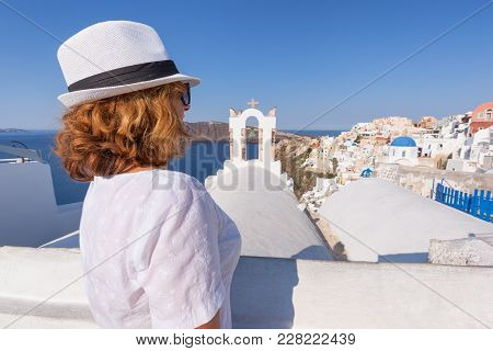 Redhead Woman Contemplating Next To The Traditional Village Oia At Sunny Day. Lifestyle And Travel C