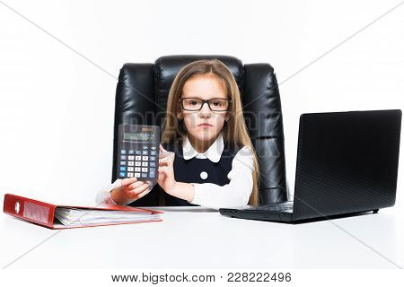Adorable Cute Angry Little Girl Sitting In Chair In Office Dressed As A Businesswoman Working On Lap